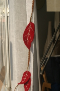 Houseproud homestead projects - close-up of leaves strung on a garland of red flannel flags and red felt leaves.