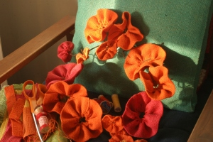 """Work in progress - burlap flowers and wreath form (being kept company by thread, """"needle girl"""" and some scraps of burlap)."""