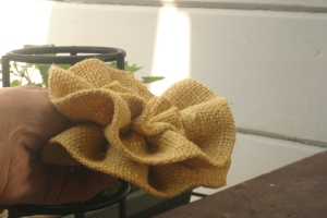 Side-view close-up of yellow burlap flower to be used in fall-inspired wreath