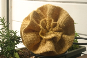 A yellow burlap flower that will be used in a fall-inspired wreath.