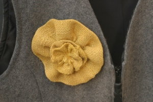 I made a lovely little flower pin out of some of the yellow burlap flowers that I have been playing around with (the burlap flowers that will eventually turn into a fall-inspired wreath for the Houseproud homestead's living room).  The back of the pin looks almost as finished as its front.
