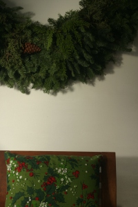 We  don't have enough room in our tiny apartment for a tree, so we hang wreaths or fir boughs instead.  I hung a HUGE wreath on the wall next to the tv this year.  I was going to decorate the wreath, but I decided to keep it bare.  It's quiet, unlike the santas and the elves.  The wreath smelled SO good when I first brought it into the house - like being in a forest.  I still get a whiff of forest when I walk past it.  Mmmmm, I do like that smell ...
